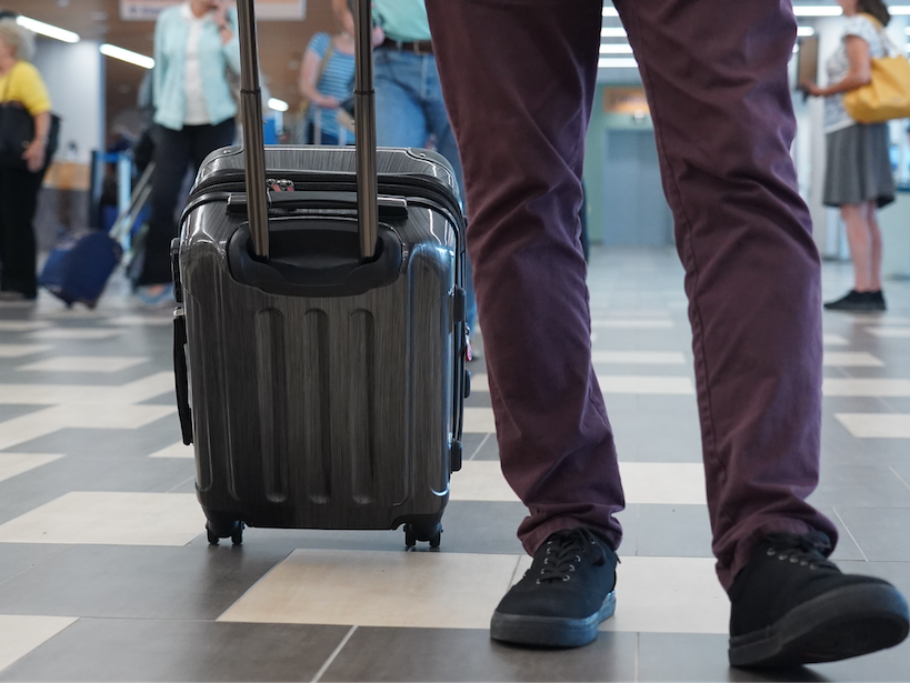 photo of businessman with luggage walking through airport
